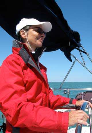 Anita at the helm of her sailboat testimonial