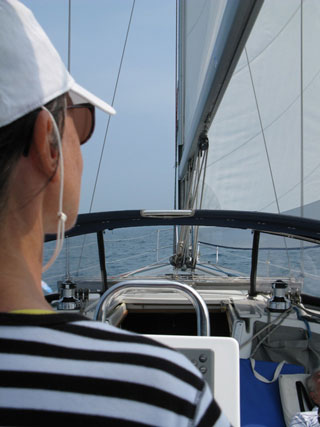 Anita from behind steering sailboat testimonial