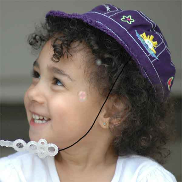 Child wearing baseball cap and Capsurz® under chin