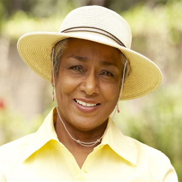 Woman wearing wide-brimmed hat Capsurz® under chin