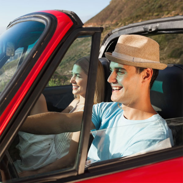 Couple driving convertible and Capsurz® under chin
