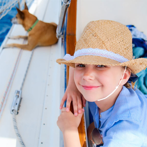 Girl boating in straw hat with Capsurz® under chin