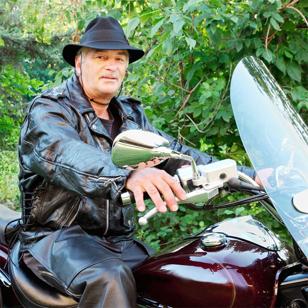 Man on motorcycle wearing Capsurz® and fedora