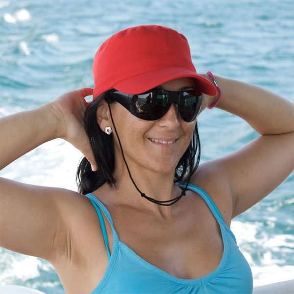 Woman in baseball cap poolside Capsurz® under chin